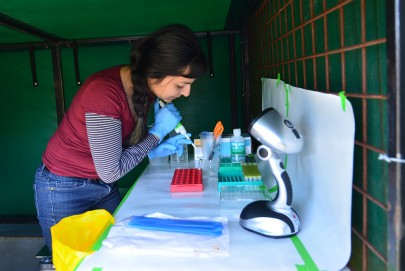 Manpreet Dhami working in the mobile lab in a field near Taupō