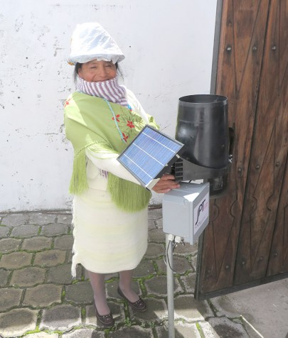 A woman from the local community with on of the original recording rain gauges (now more reliable solar charging and connected to web).