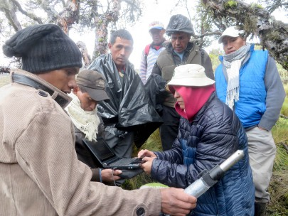 Marcia Chancusig (CESA) with Toacaso community members downloading river level data at a river monitoring site under Volcan Illinizas for planning a water supply scheme.