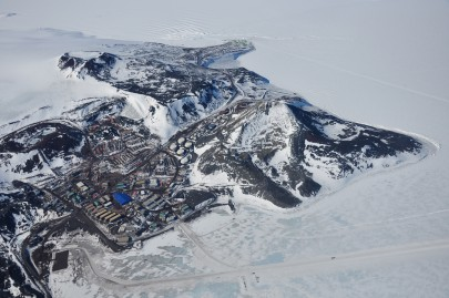 Aerial photograph of McMurdo Station (US, foreground) and Scott Base (New Zealand, green buildings at top).