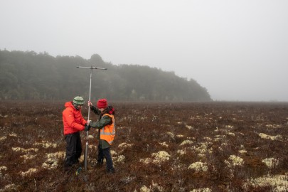 Researchers Jamie Wood and Michelle McKeown collecting a wetland soil core.